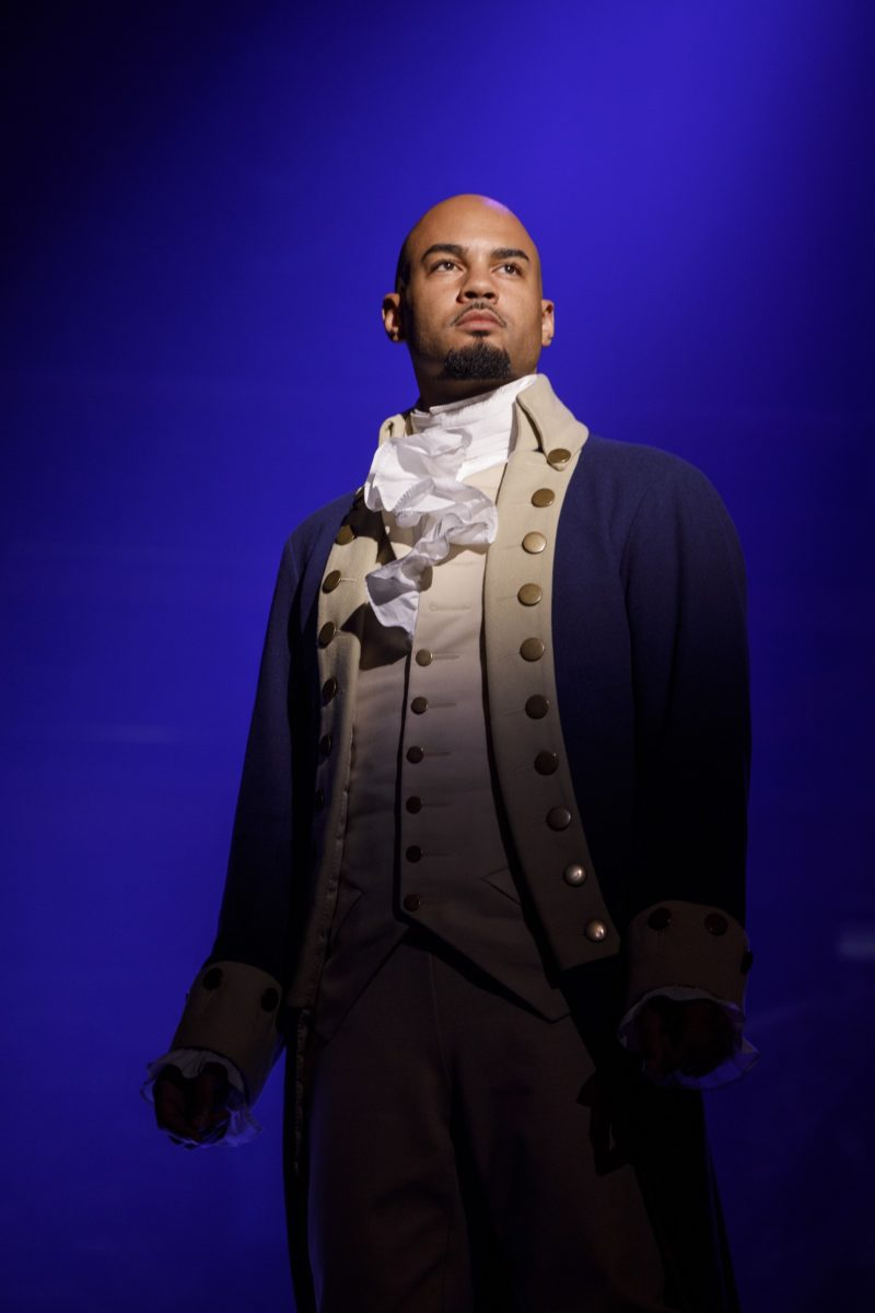 "Aaron Burr stands alone on stage singing ""Wait For It."""