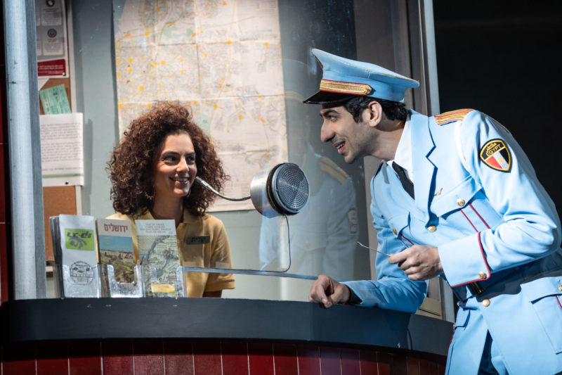 A member of the Alexandria Ceremonial Police Orchestra asks for help from the woman at the information booth at the bus station in THE BAND'S VISIT