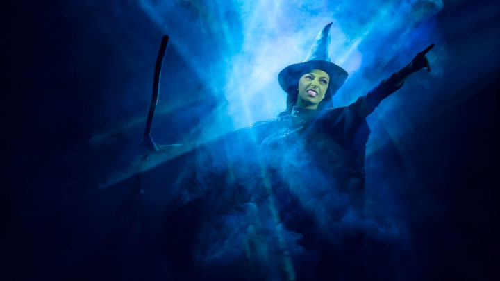 A woman (Elphaba - the Wicked Witch of the West) with green skin wearing a witch's hat holds a broom in her right hand while pointing with her left while flying